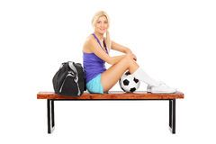 Jogador de futebol fêmea que senta-se em um banco Imagens de Stock