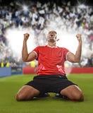Jogador de futebol feliz e entusiasmado no jérsei vermelho que comemora marcando o objetivo que ajoelha-se no passo da grama Imagens de Stock
