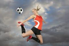 Jogador de futebol fêmea que retrocede uma esfera Fotografia de Stock Royalty Free