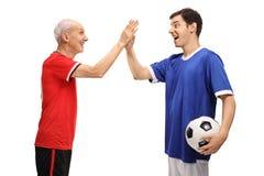 Jogador de futebol idoso e fiving alto do jogador de futebol novo Fotos de Stock Royalty Free