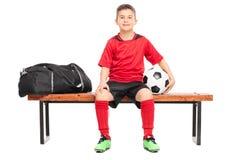 Jogador de futebol júnior que senta-se em um banco imagem de stock royalty free