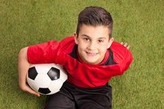 Jogador de futebol júnior que senta-se na grama e no sorriso fotografia de stock