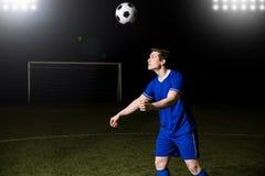 Jogador de futebol masculino que dirige uma bola fotografia de stock