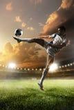 Jogador de futebol na ação no fundo do estádio do por do sol Fotografia de Stock