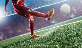 Jogador de futebol na bola do pontapé da ação no estádio Fotografia de Stock