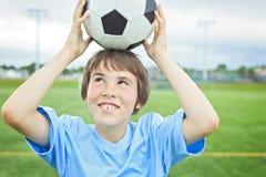 Jogador de futebol novo com a bola no campo Fotos de Stock