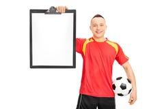 Jogador de futebol novo que guarda uma prancheta Imagens de Stock