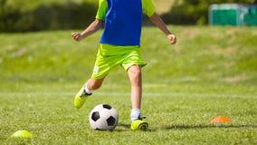 Jogador de futebol novo que retrocede a bola no passo do futebol Imagens de Stock Royalty Free