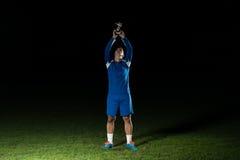 Jogador de futebol que comemora Victory While Holding Win Coup Fotografia de Stock Royalty Free