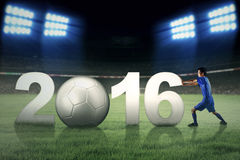 Jogador de futebol que empurra os números 2016 no campo Fotos de Stock