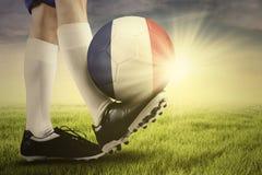 Jogador de futebol que exercita com bola fora Imagens de Stock Royalty Free