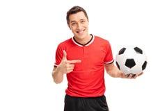 Jogador de futebol que guarda uma bola e que aponta a ela Imagens de Stock