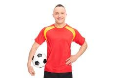 Jogador de futebol que guarda uma bola e um sorriso Fotografia de Stock Royalty Free