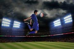 Jogador de futebol que joga uma bola na noite Fotos de Stock