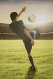 Jogador de futebol que joga uma bola no campo Imagem de Stock