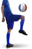 Jogador de futebol que joga uma bola no estúdio Fotos de Stock Royalty Free