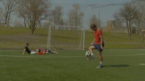 Jogador de futebol que salta a bola de futebol com pés video estoque