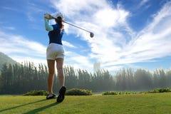 Jogador de golfe asiático da mulher que faz o T do balanço do golfe fora no tempo verde da noite no fundo do céu azul Faz presumi fotografia de stock royalty free