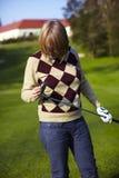Jogador de golfe da mulher nova que examina seu clube de golfe Imagem de Stock Royalty Free
