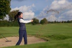 Jogador de golfe da mulher que joga fora de um depósito da areia Foto de Stock