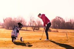 Jogador de golfe da mulher que joga um círculo na luz solar da noite Fotos de Stock