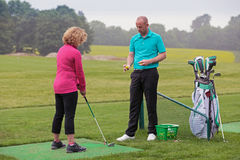 Jogador de golfe da senhora que está sendo ensinado por um pro de golfe. Foto de Stock Royalty Free