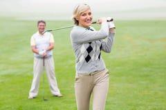 Jogador de golfe da senhora que teeing fora para o dia olhado pelo sócio Foto de Stock