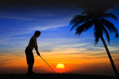 Jogador de golfe da silhueta no por do sol Fotos de Stock Royalty Free
