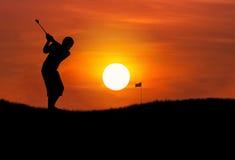 Jogador de golfe da silhueta que bate a bola de golfe no por do sol Imagem de Stock Royalty Free
