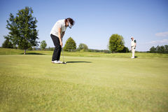 Jogador de golfe de dois séniores no verde. Imagens de Stock