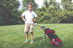 Jogador de golfe do rapaz pequeno com seu saco de golfe no fairway foto de stock
