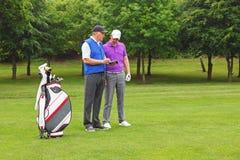 Jogador de golfe e transportador que olham um guia do curso Fotos de Stock