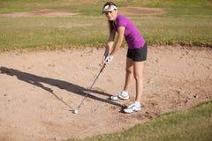 Jogador de golfe fêmea em uma armadilha de areia Fotografia de Stock Royalty Free