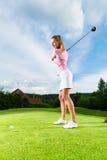 Jogador de golfe fêmea no curso que faz o balanço do golfe Fotografia de Stock Royalty Free
