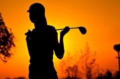 Jogador de golfe fêmea no nascer do sol Foto de Stock