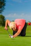 Jogador de golfe fêmea novo no curso que aponta para posto Foto de Stock Royalty Free