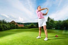 Jogador de golfe fêmea novo no curso que faz o balanço do golfe Fotografia de Stock