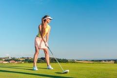 Jogador de golfe fêmea profissional que sorri ao balançar um clube do motorista foto de stock royalty free