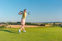 Jogador de golfe fêmea profissional que sorri ao balançar um clube do motorista imagens de stock
