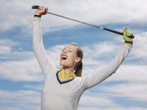 Jogador de golfe fêmea que mantem o clube contra o céu Fotografia de Stock