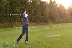 Jogador de golfe fêmea que pratica em um driving range fotografia de stock