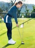 Jogador de golfe fêmea que prepara-se para bater a bola fotografia de stock royalty free