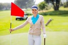 Jogador de golfe fêmea que sorri na câmera e que guarda seu clube de golfe Foto de Stock