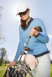 Jogador de golfe fêmea que toma o clube de golfe Foto de Stock