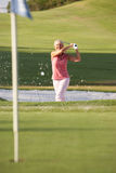 Jogador de golfe fêmea sênior que joga o tiro do depósito Imagens de Stock
