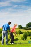 Jogador de golfe fêmea novo no curso Fotos de Stock Royalty Free