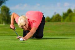 Jogador de golfe fêmea novo no curso que aponta para posto Imagem de Stock