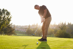 Jogador de golfe masculino que põe a bola no furo sobre o verde Imagens de Stock