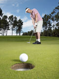 Jogador de golfe masculino que põe a bola sobre o verde Foto de Stock