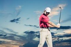 Jogador de golfe no por do sol Fotografia de Stock